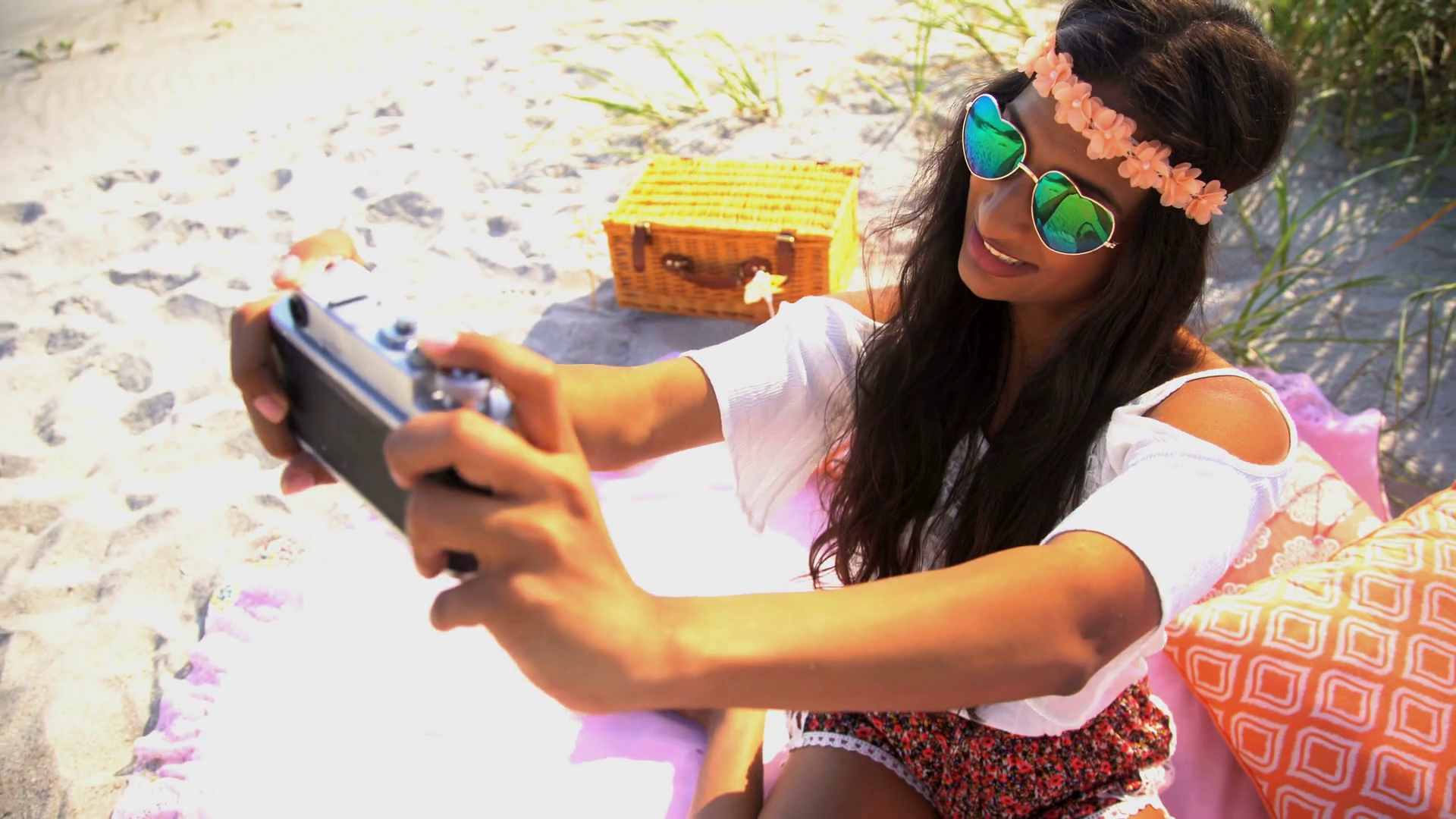 young-smiling-indian-american-woman-in-bohemian-style-sun-dress-taking-selfie-at-picnic-on-her-beach-holiday_rleyvwiqe_thumbnail-full01